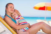 Relaxed mother on sun bed embracing baby — Stock Photo