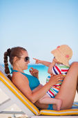 Mother with baby on beach playing with sunglasses — Stock Photo
