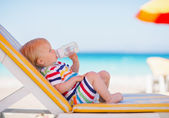 Portrait of baby on sunbed drinking water — Stock Photo
