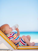 Portrait of baby on sun bed drinking water — Stock Photo