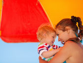 Portrait of mother and baby on beach under umbrella — Stock Photo