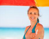 Happy woman applying sun block creme on arm — Stock Photo