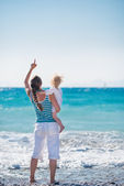 Mother and baby on sea coast pointing on copy space — Stock Photo
