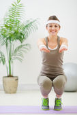 Smiling woman in sports wear squatting — Stock Photo
