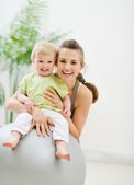 Portrait of happy mother and baby in gym — Stock Photo