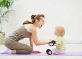 Baby helping mother lifting dumb-bells — Stock Photo