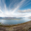 Stock Photo: Fjord surrounded by mountains bathing in evening light