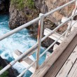 Stock Photo: Wooden bridge over wild water canyon