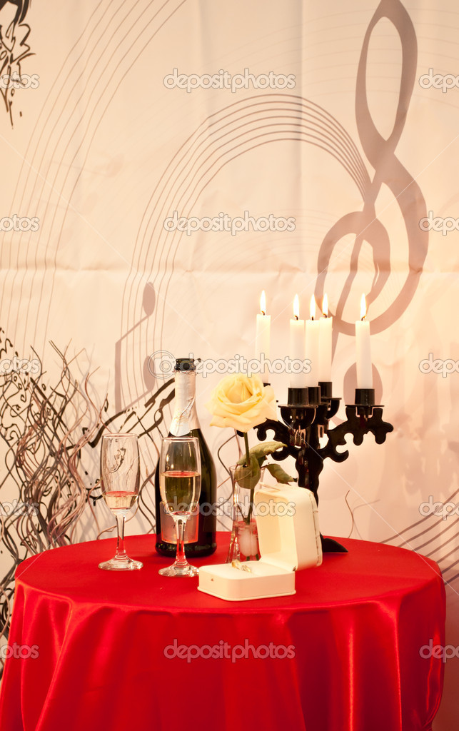 A table decorated with candles, rose,glasses, champagne and wedding ring. A perfect atmosphere for declarations of love and a marriage proposal.  Stock Photo #11226999