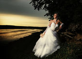 The bride admiring the sunset at the riverside — Stock Photo