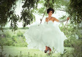 Smiling bride on the swings, countryside background — Stock Photo