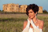 Portrait of cute brunette bride with the ruins on the background, at sunset — Stock Photo