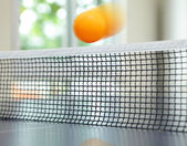 Orange table tennis ball moving over net — Stock Photo