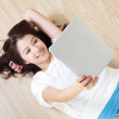 Girl lying and smile using tablet pc at home — Stock Photo