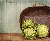 Artichokes spilling out of a basket — Stock Photo
