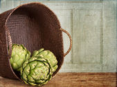 Artichokes spilling out of a basket — Stockfoto