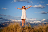 Little girl jumping in a mountain landscape — Stock Photo