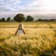 Girl or teen walking through wheat field — Stock Photo