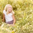 Girl sitting in wheatfield — Stock Photo