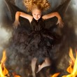Young dark angel rising from the flames — Stock Photo