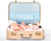 Baby yawning in a suitcase — Stock Photo