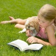 Girl reading with dog outdoors — Stock Photo