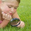 Girl looking through magnifying glass outdoors — Stock Photo