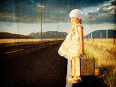Young girl on side of road with suitcases — Stock Photo