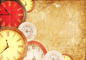 Many clocks on a paper background — Stock Photo