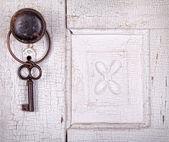 Vintage key hanging on a vintage door — Stock Photo