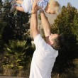 Stock Photo: Young infant lifted by father