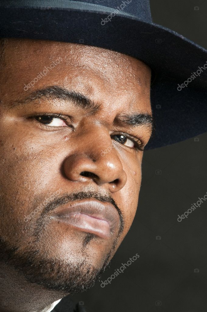 Young serious African American man wearing a fedora over a gray background  Stock Photo #10972441