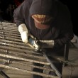 Metal worker finishing welds with a grinder — Stock Photo #11099039