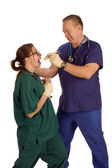 Mad dentist pulling tooth from nurse — Stock Photo