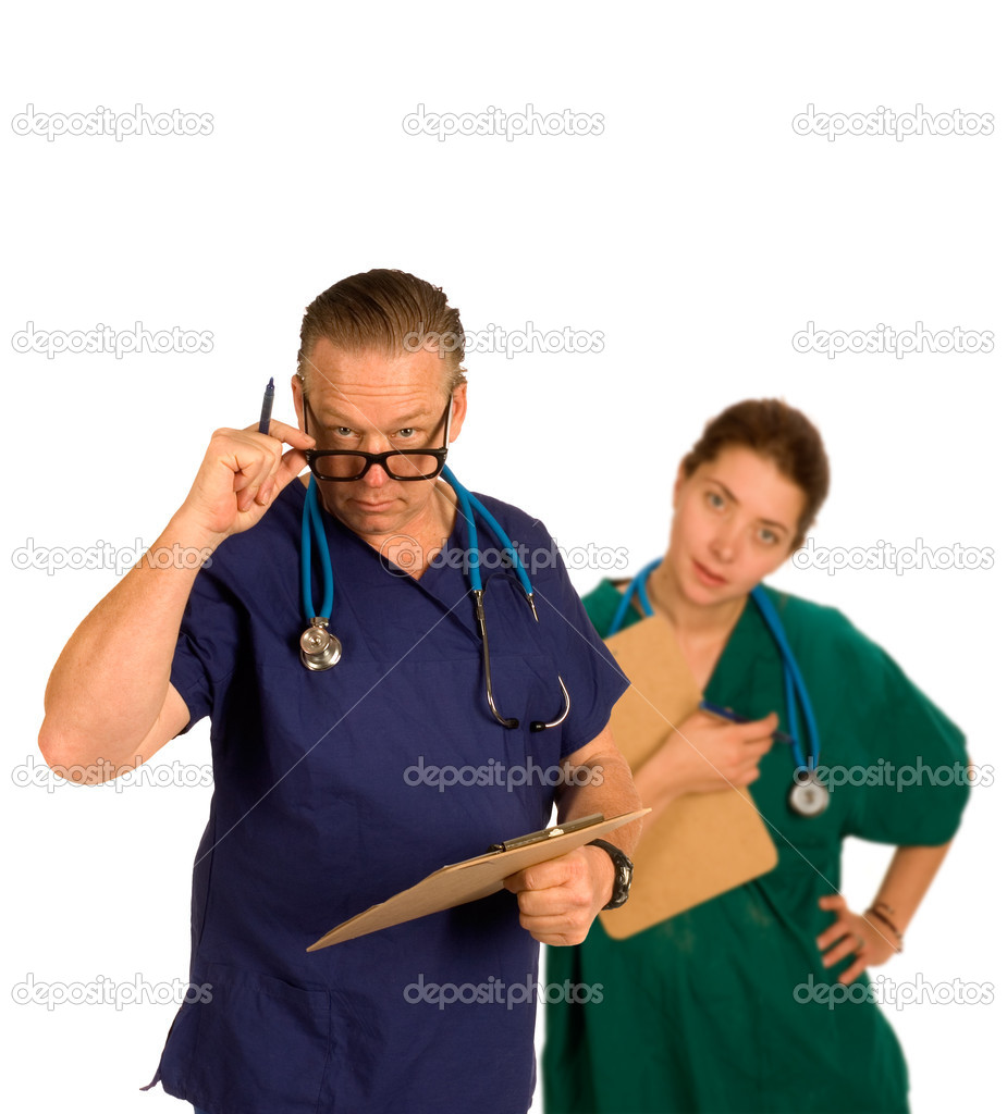 Doctor in forground having just checked chart id questioning with intern standing behind slightly out of focus, both with steoscopes around neck — Stock Photo #11099107