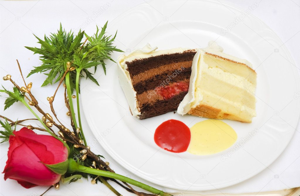 Slices of wedding cake with two layers one chocolate and one white on a white plate with a rose — Stock Photo #11113712
