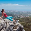 Young athletic girl relaxing on top of rocks — Lizenzfreies Foto