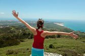 Fitness girl on top of rocks with arms wide open — Stock Photo