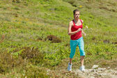 Fitness girl running on path in mountains — Stock Photo