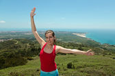 Fitness girl on top of rocks with arms wide open — Stockfoto