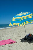 Blue and yellow umbrella on a sandy beach — Stok fotoğraf