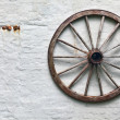 Rustic wagon wheel hanging on a wall — Stock Photo #11503448