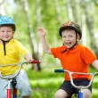 Happy children on bicycle in green park — Stock Photo