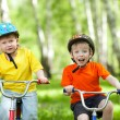 Happy children on bicycle in green park — Stock Photo #10880868