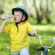Cute child kid on bicycle and drinking  water fom bottle — Zdjęcie stockowe