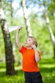 Mignon garçon tenant un avion en papier dans le parc — Photo