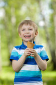 Young boy eating a tasty ice cream outdoor — Stock Photo