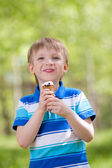 Young smiling kid eating a tasty ice cream outdoor — Stock Photo