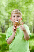 Kid eating a tasty ice cream outdoor and showing thumb up — Stockfoto