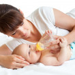 mladá matka krmení její rozkošné dítě — Stock fotografie